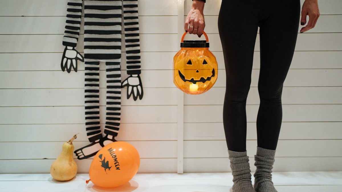 two people holding jack o lantern pales. dressed in black and white