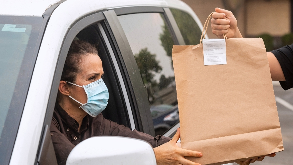 a woman wearing a mask grabs her bag, accepting her curbside pickup order.