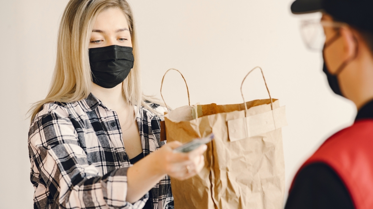 a woman accepting a home delivery order, wearing a mask