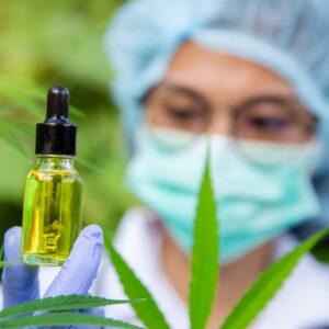Scientist wearing a mask and hairnet studying a cannabis tincture